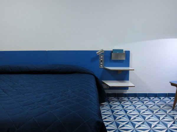 The 96 rooms face either the park or the ocean, and they are all outfitted with nearly identical furnishings, including these custom-designed headboards covered in blue laminate. Buttons to the side operate the mechanical louvers and bedside lights.