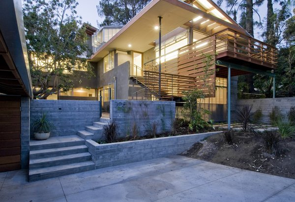 Up the drive to a two-car cover and parking area, a set of concrete stairs leads to a central patio. Retaining walls are optimized with cast-concrete seams and planting beds filled with native grasses, lending texture and interest. It's another flight up the brazilian cherry wood stairs to the front entry. Two mature trees were maintained onsite, the Brazilian Pepper lends shade to an outdoor all-purpose area.  [Photo Credit: Josh Perrin]