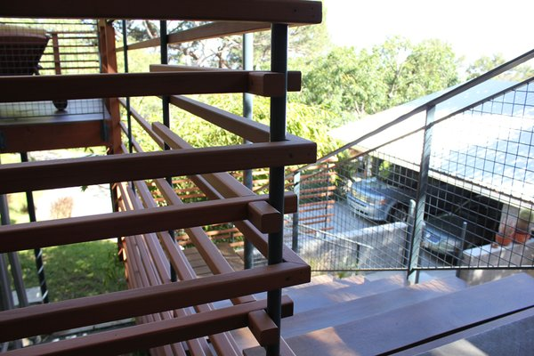 Detail of entry stair highlights the patterning of redwood and steel grid with a birch rail, giving view through to the front balcony and down to the carport. [Photo Credit: Jodie Bass]