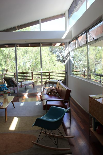 The main living room area is filled with light from the South and East, overlooking a valley of Mount Washington towards Montecito Heights. The teal rocker and storage unit at right are Eames designs, the leather sofa was salvaged from a public school, the coffee table a mid-century Modern find, and the deck loungers were purchased from restoration hardware. Brazilian Cherry wood floors partially covered with wool rug from Christopher Farr.  [Photo Credit: Jodie Bass]