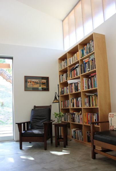 "Current owners melded their former dwelling's period furnishings—an L. & J.G. Stickley settee at right, William Morris attributed chair, and Handel lamp—with their new setting.  The reading area is ""an homage to our craftsman home we left to live here,"" says owner Allison Morgan.  Hanging above, a work by Georgia-based artist Kathleen West, known for her contemporary take on Arts and Craft style block print, links past with present. [Photo Credit: Jodie Bass]"