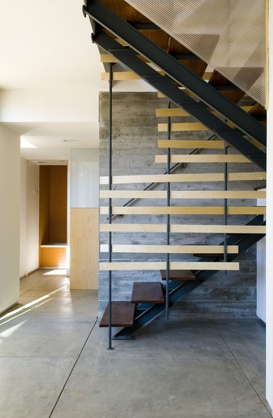 Interior stairs serve as a thermal chimney and light well, providing ventilation as well as illumination at all levels.  [Photo Credit: Josh Perrin]