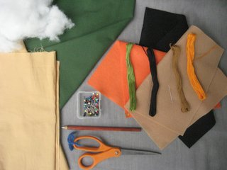 Materials! Here's what you'll need to make it happen:<br><br>1/3 yard green fabric. I used a light cotton twill, but Bonnie used fleece in the book. Anything goes!<br><br>1/4 yard tan fabric<br><br>Orange, black, and tan felt. I bought a square of each, but you don't use much!<br><br>Embroidery floss in green, black, orange, and tan<br><br>Scissors<br><br>Straight pins<br><br>Chalk or white charcoal pencil (optional)<br><br>Sewing machine (optional)