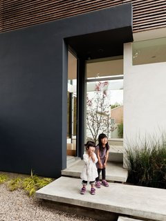 Yumi (left) and Maya (right) cheese around on the steps leading into the front door. Inside, there is ample space for removing and leaving one's shoes, another Japanese element.