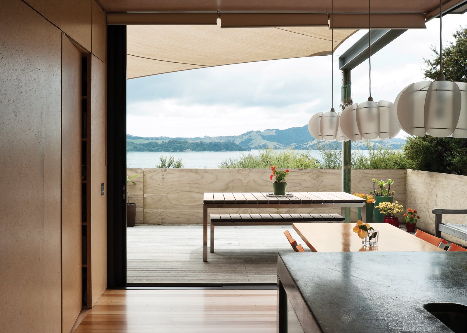 The north-facing doors slide completely away to open the house to the outdoors, offering an uninterrupted view of the water. The pendant lights over the table are from Iko Iko.  Photo 2 of 25 in Make Your Parents Happy by Building Them a House