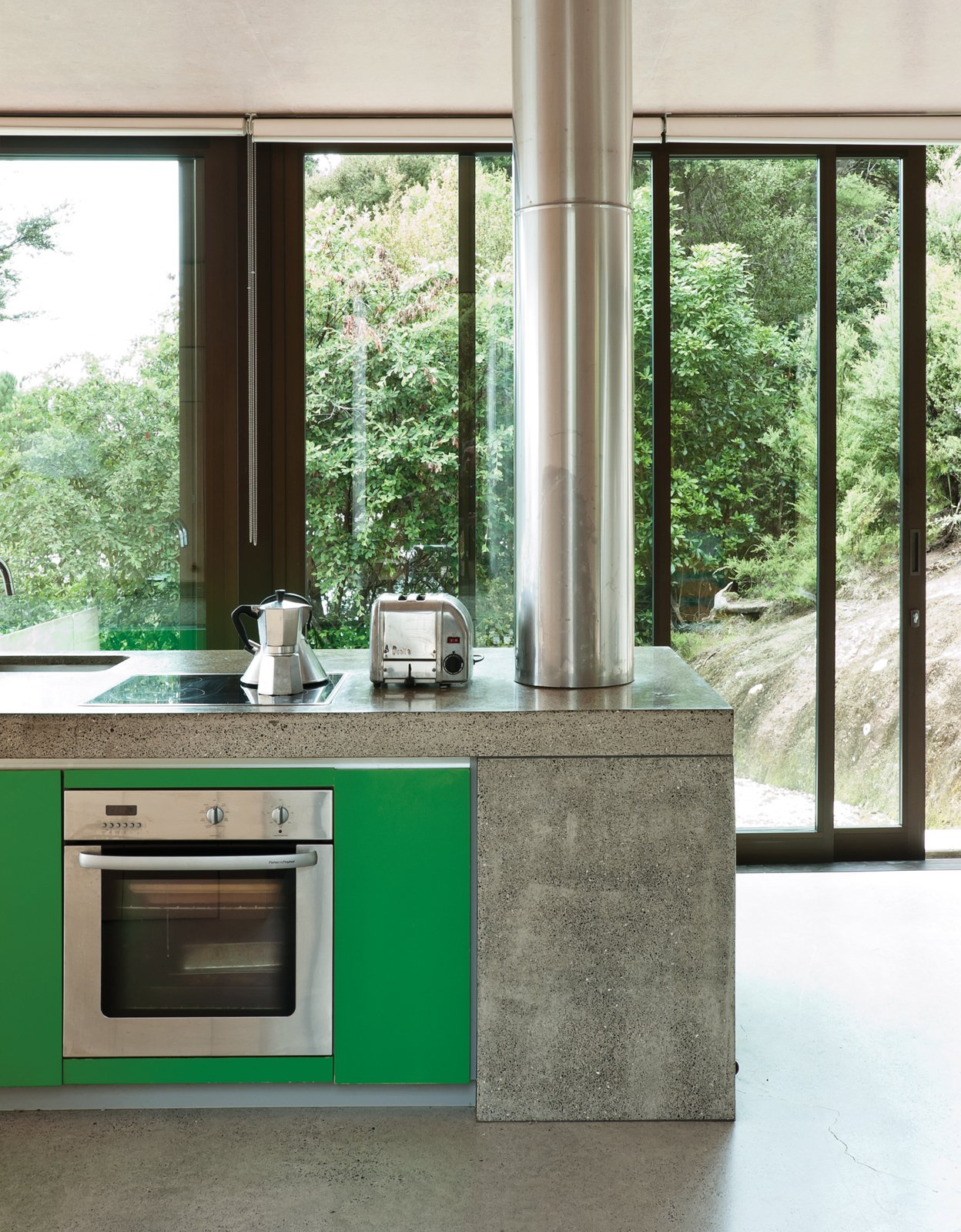 A pop of color in the kitchen cabinets refers to the native greenery outside. Tagged: Kitchen, Concrete Counter, Cooktops, and Wall Oven.  Photo 3 of 25 in Make Your Parents Happy by Building Them a House