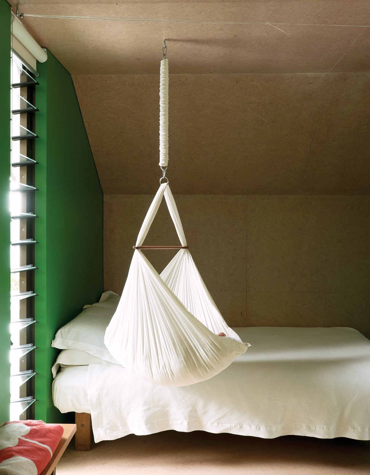 For now, one-year-old Awa is small enough to sleep in the hammock that hangs from the ceiling. Tagged: Bedroom and Bed.  Bedrooms by Dwell from Make Your Parents Happy by Building Them a House