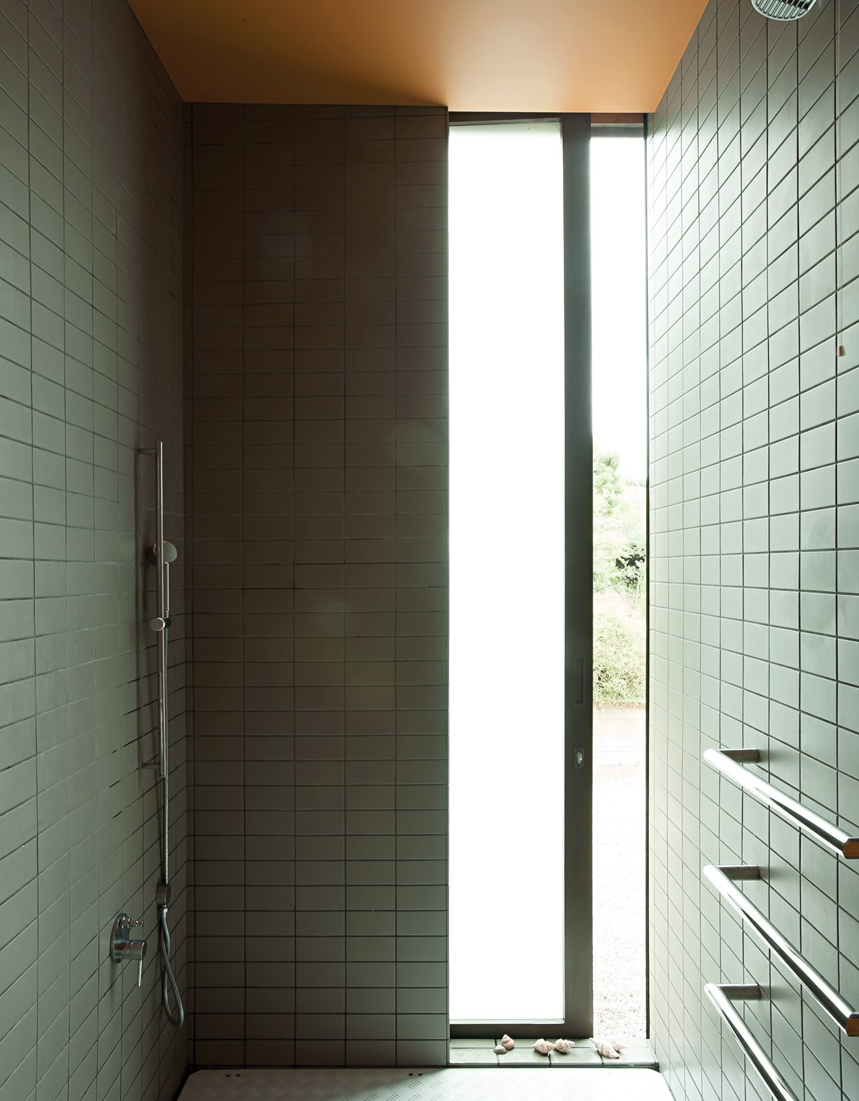The shower provides a glimpse of the outdoors. Tagged: Bath Room, Ceramic Tile Wall, Open Shower, and Full Shower.  Photo 13 of 25 in Make Your Parents Happy by Building Them a House