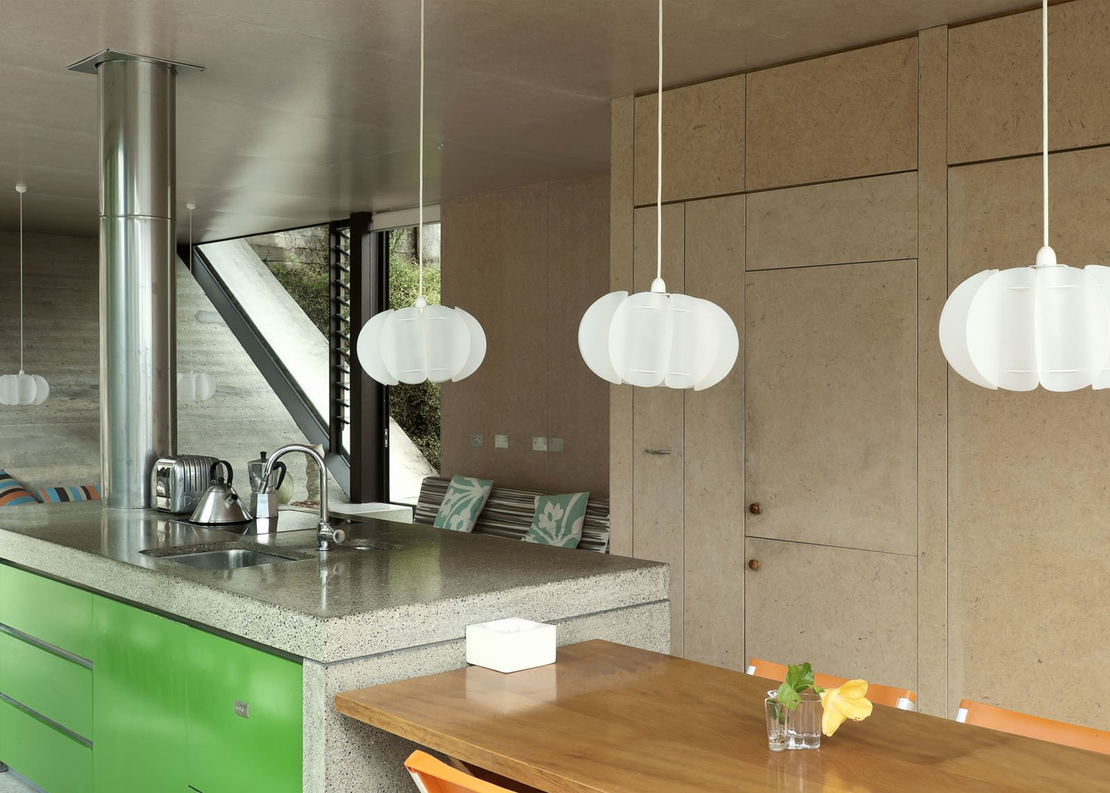 The hanging Iko Iko pendants in the kitchen add a vertical touch to a space and help frame the views outside.  Photo 21 of 25 in Make Your Parents Happy by Building Them a House