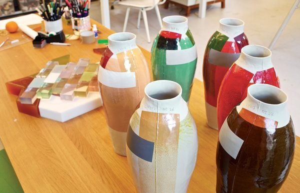 On a work table, a cluster of early color experiments foretells her 300 Unique Vases project.