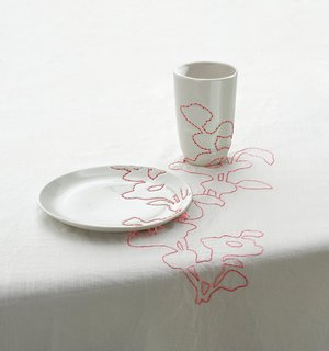 1999<br><br>Embroidered Tablecloth continues patterns derived from Ming vases across plates and cups.