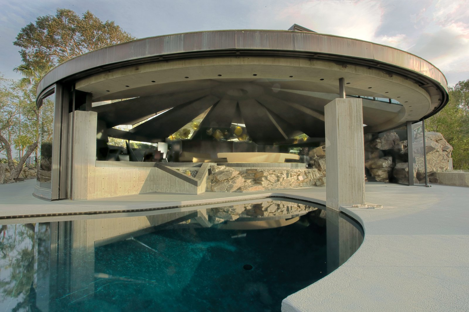 Key features of the Elrod House include a circular concrete construction, retractable glass walls,  and a swimming pool that sweeps into the living space. Tagged: Outdoor, Swimming Pools, Tubs, Shower, Hardscapes, and Concrete Fences, Wall.  Photo 5 of 5 in A House Worthy of James Bond and More from The Midcentury Architecture of California Modernist John Lautner