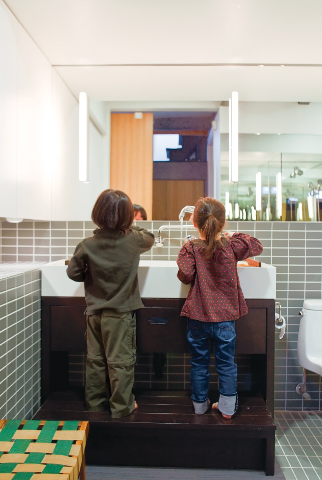 In the bathroom, the twins take advantage of a custom-built Corian sink and wooden base with integrated step when it's time to wash up.  Photo 3 of 13 in Play's the Thing