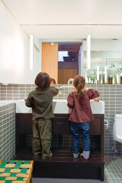 In the bathroom, the twins take advantage of a custom-built Corian sink and wooden base with integrated step when it's time to wash up.