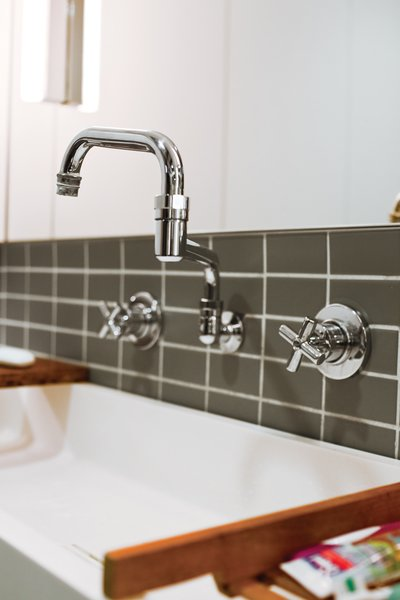 """Double Jointed  In the downstairs bathroom, John chose a """"potwasher"""" fixture by Encore that's often used in restaurant kitchens. Its double-jointed arm lets it reach every corner of the custom Corian sink, where all five family members wash up—sometimes at the same time.  componenthardware.com"""