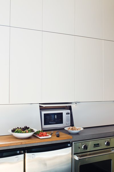 """Behind Closed Drawers  To continue the spare lines of the kitchen cabinets, John designed and built an """"appliance garage"""" by cutting up Ikea drawer fronts to build hinged doors that enclose an area beneath the cabinets, hiding a toaster, microwave, breadbox, and electrical outlets.  ikea.com"""