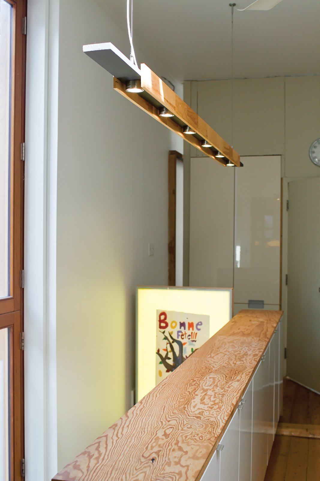 """Buddy Hacked It  The light fixture hanging over the stairs to the playroom is another Ikea hack: The hanging hardware is actually for curtains, and the six Grundtal lights are meant to be hung under cabinets. They're mounted on a horizontal three-quarter-inch-thick piece of pine, and two other slats hang vertically along the two sides. """"It's really an afternoon project,"""" says John.  Photo 12 of 13 in Play's the Thing"""