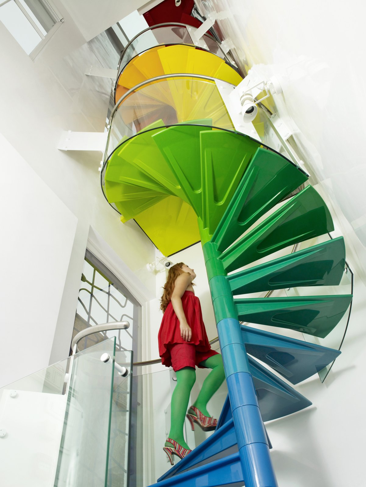 """The staircase is the hub, the soul of the project,"" Rogers says. ""It's meant to be enjoyed."" From the ground, the steps start with the cool colors of the earth, then get warmer as they reach up to the sky.   Tagged: Staircase and Metal Railing.  Photo 5 of 6 in A Family Goes Somewhere Over the Rainbow"