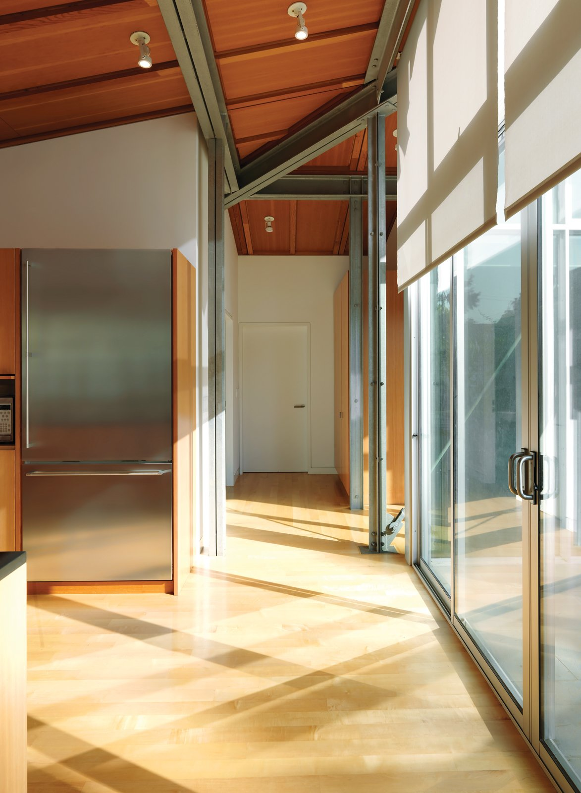 The architecture mixes Douglas fir beams and exposed steel framing, achieving its soaring spaces without pretentiousness. Tagged: Kitchen, Refrigerator, and Wood Cabinet.  Photo 5 of 16 in Family Matters