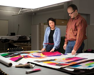 Studio member Eri Shimatsuka (left) and studio manager Petri Juslin (right) compare a first fabric proof to the artist's original drawing.