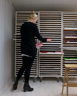 Next, the screens are made, and the designer chooses the color tones. In a room next to the printing machines, a locker with narrow drawers holds numerous pieces of neatly stacked, colorful fabrics.