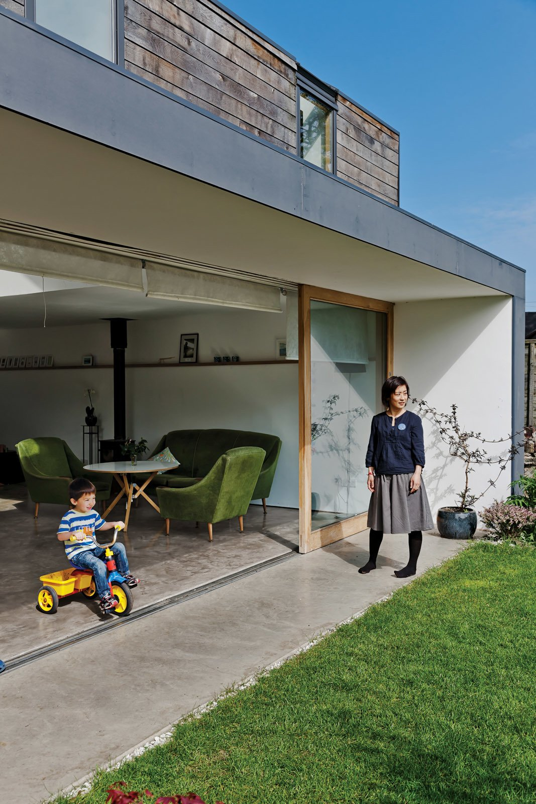 The back of the house has sliding doors that open far enough to expose the entire livingroom to the families' back yard. Tagged: Outdoor, Grass, and Back Yard.  Japanese Homes by Dwell from A Piece of Home