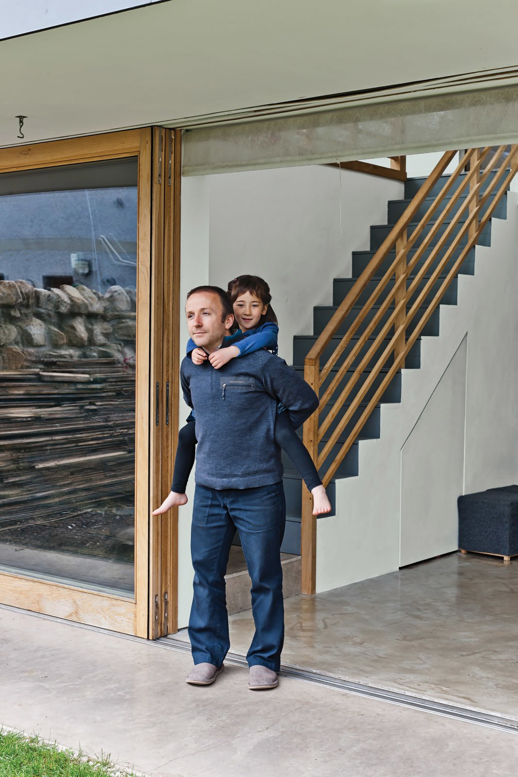 Gaffney and Kiku take in the air from the large sliding door bought from Timber Tech Scotland. Tagged: Staircase, Wood Tread, and Wood Railing.  190+ Best Modern Staircase Ideas by Dwell from A Piece of Home