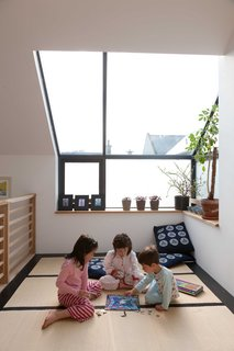 A Piece of Home - Photo 18 of 22 - Mika, Kiku, and Kaz'ma play in the tatami room beneath the big skylight. The cushions on the floor were sent from Japan by the childrens's grandmother. The tatami mats were actually purchased in the UK from the Futon Company. Gaffney notes that they're not the proper dimensions of Japanese tatami mats, but they were much less expensive than importing the real thing.