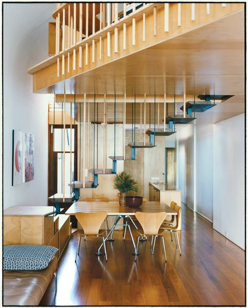 The addition's most eye-catching feature is the steel staircase with recycled blackbutt wood treads. The bottom steps double as benches to supplement the six Arne Jacobsen Series 7 dining chairs for Fritz Hansen and a Nomos table base by Sir Norman Foster for Tecno.