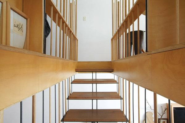 The steel-and-wood stairs lead to the master bedroom and study.