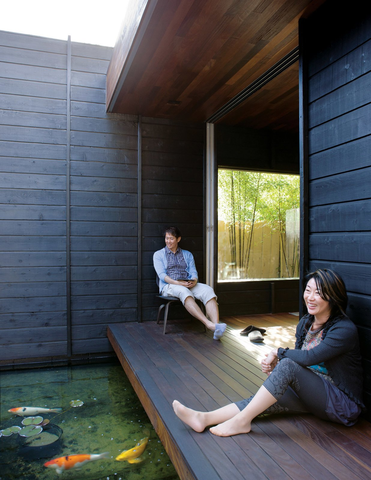 With doors open, Shino and Ken pull an Eames LCW chair for Herman Miller outside to enjoy the space. Tagged: Outdoor, Wood Patio, Porch, Deck, Small Patio, Porch, Deck, and Back Yard.  Nippon inspired by Aaron King from An Atypical Modern Home in Southern California