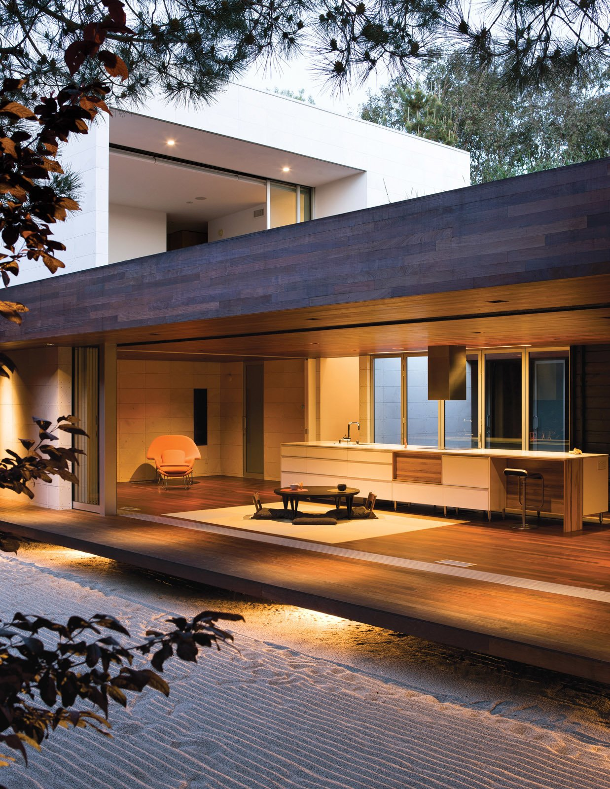 "Protected by an overhang, and floating above ground level, this tertiary space is known in traditional homes as the ""engawa."" To sustain a unified look throughout, the floor and ceiling are clad in ipe wood.  Tagged: Living Room, Coffee Tables, Chair, and Medium Hardwood Floor.  Kitchen by Lara Deam from An Atypical Modern Home in Southern California"