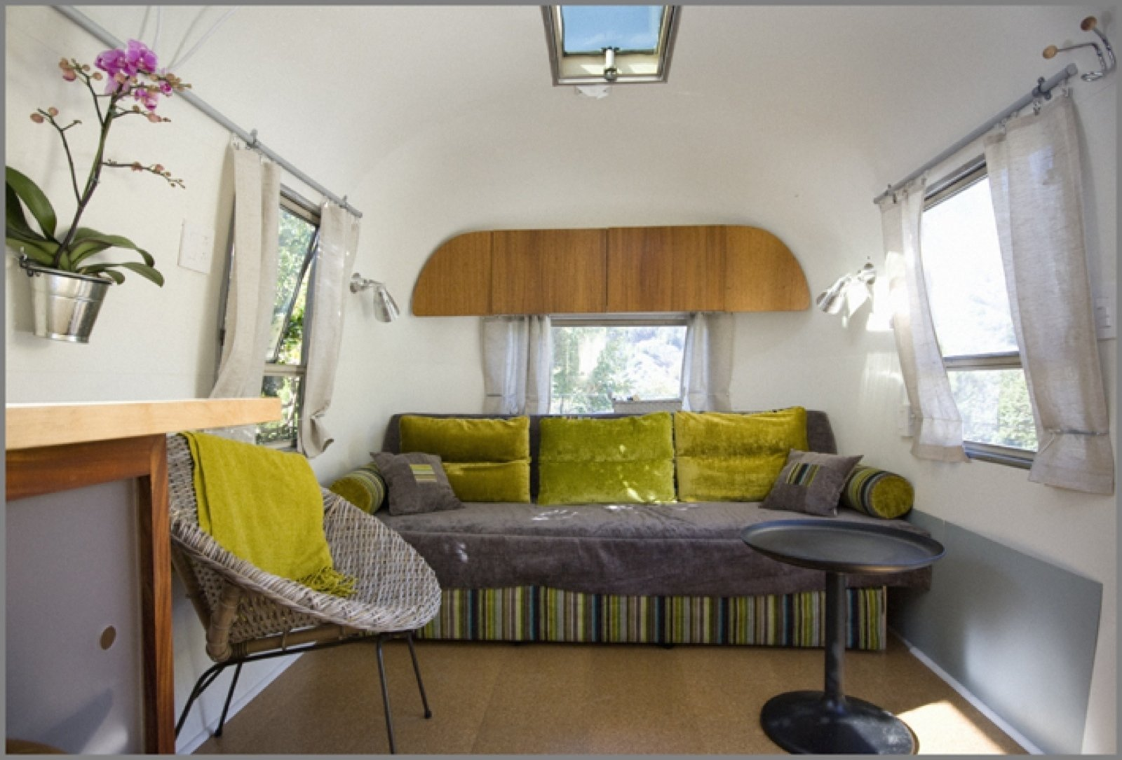 Here's the finished sofa bed. The sofa is upholstered in Designers Guild fabric. The curtains are from Ikea. The chair is from Cost Plus. And the wall cupboard above incorporates some of the trailer's original mahogany wood.  8 Ways to Renovate an Airstream by Erika Heet from Big Sur Airstream Renovation