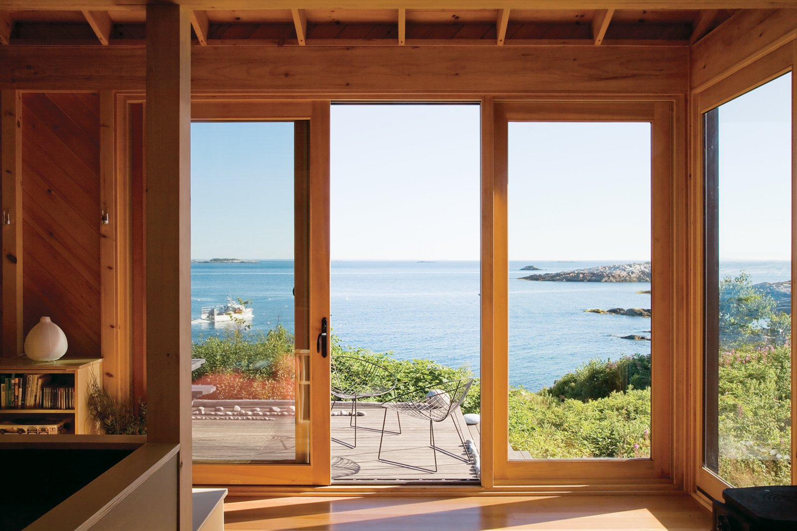 The porch at writer Bruce Porter's off-the-grid retreat on Ragged Island, Maine, boasts Leaf chairs by Arper as well as dreamy views.  Photo 8 of 11 in Take it Outside With These 11 Spring-Friendly Deck Spaces from Seven Great Outdoor Spaces