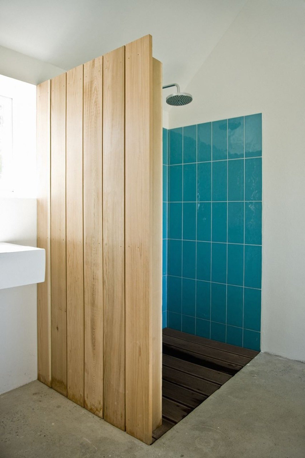 """Colored tiles in the shower are revealed behind a cedar wood wall. """"The sound of falling water on wood and the surrounding fields form the background,"""" say the architects. """"This was our way of introducing an immaterial idea of what luxury actually could be about.""""  Barn Renovation Ideas by Miquel Sune from An Idyllic Swedish Summerhouse"""