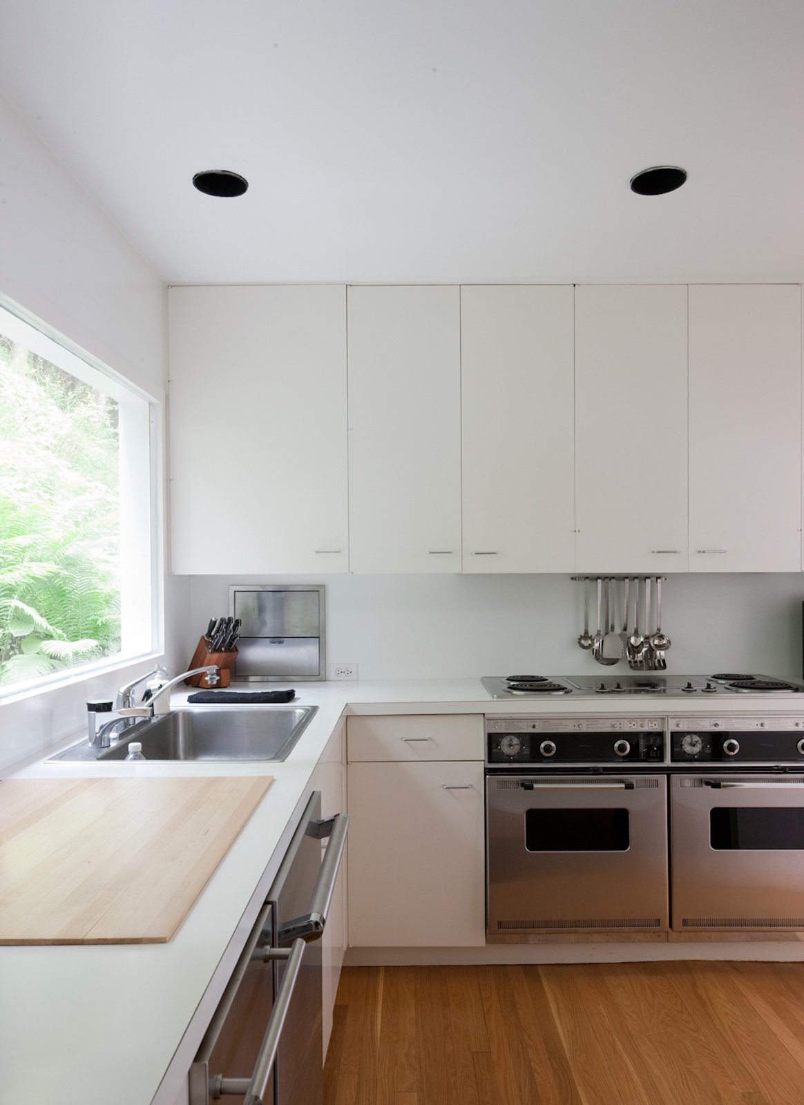 "The ""Meier white"" extends even to the kitchen, which has been updated with new appliances.  Photo 19 of 22 in This Lake House Is a Living Piece of Architecture History"