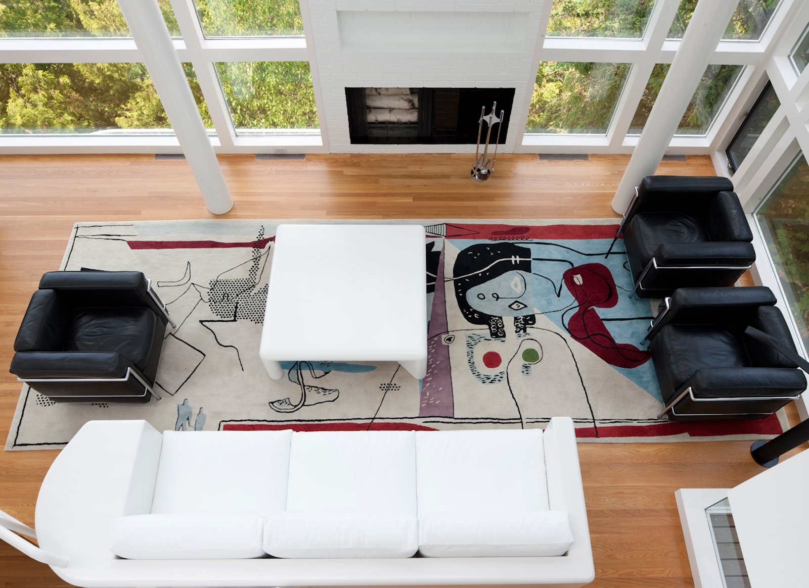 The view overlooking the living room, which features the famous Le Corbusier rug by Edward Fields. The residents were also careful to save the sofa, which Meier himself designed for the space.  How to Frame Space With a Graphic Rug by Aileen Kwun from This Lake House Is a Living Piece of Architecture History