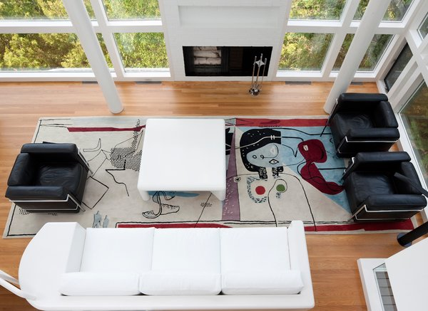 This Lake House Is a Living Piece of Architecture History - Photo 19 of 21 - The view overlooking the living room, which features the famous Le Corbusier rug by Edward Fields. The residents were also careful to save the sofa, which Meier himself designed for the space.