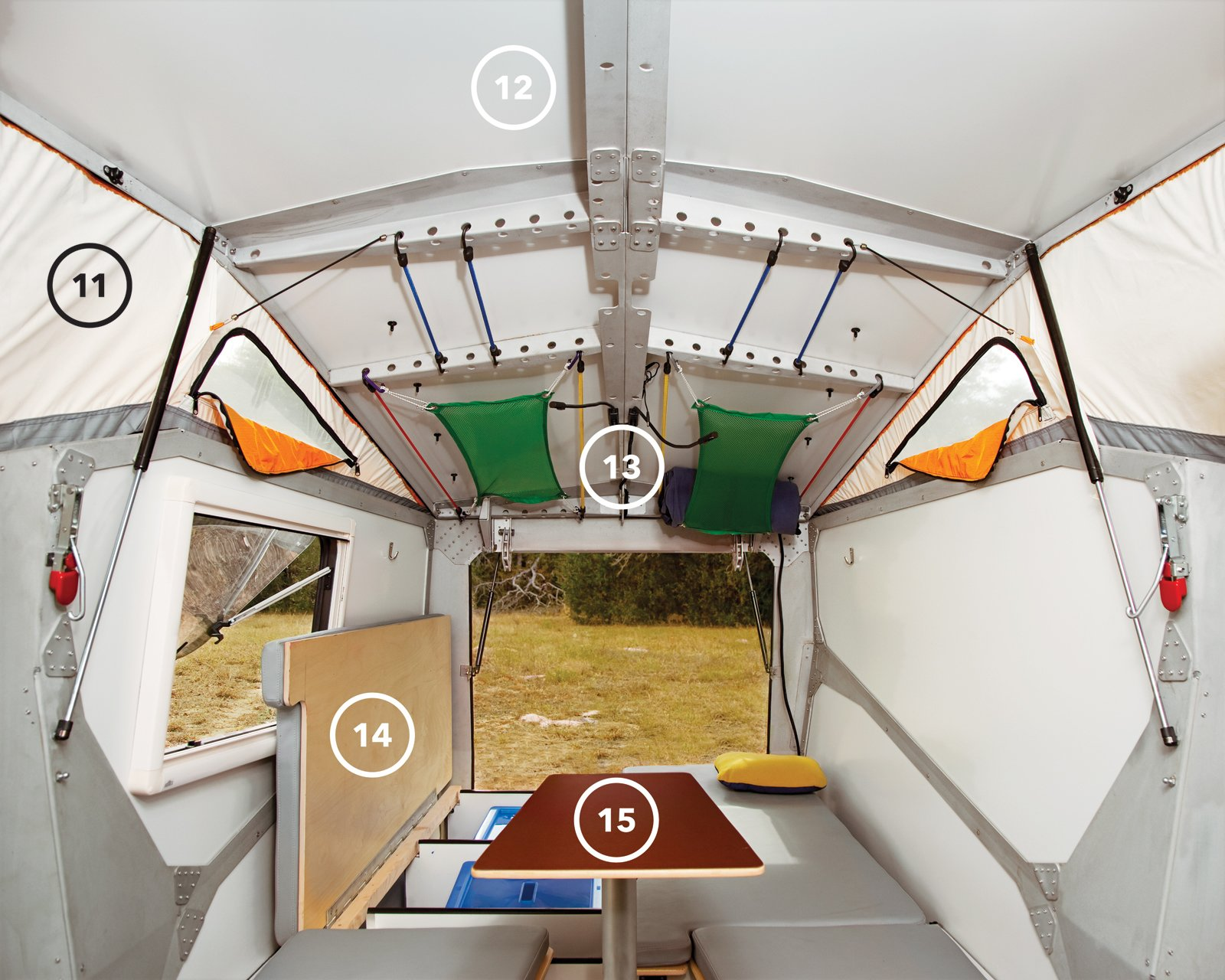 While the front, kitchen-end of the camper is all action, the back half is about rest and relaxation. The benches hide storage space beneath and, at night, become the sleeping area (14). The multiheight table (15) serves as an eating spot when in its highest position and as extra sleeping space when lowered and covered with a cushion. The table and its post can also be completly removed for additional legroom. The mesh-lined windows in the tent enclosure (11) bring in light and encourage ventilation. The LED reading lights (13) can be set to white or red (the latter keeps your eyes from dilating so you can run outside at a moment's notice and catch a glimpse of a shooting star without waiting for your eyes to adjust). The laser-cut aluminum frame (12) features circular openings that make hanging sleeping bags, pillows, blankets, and luggage as easy as stretching and hooking elastic cords into place. Modern NASA-Inspired Cricket Trailer - Photo 3 of 15