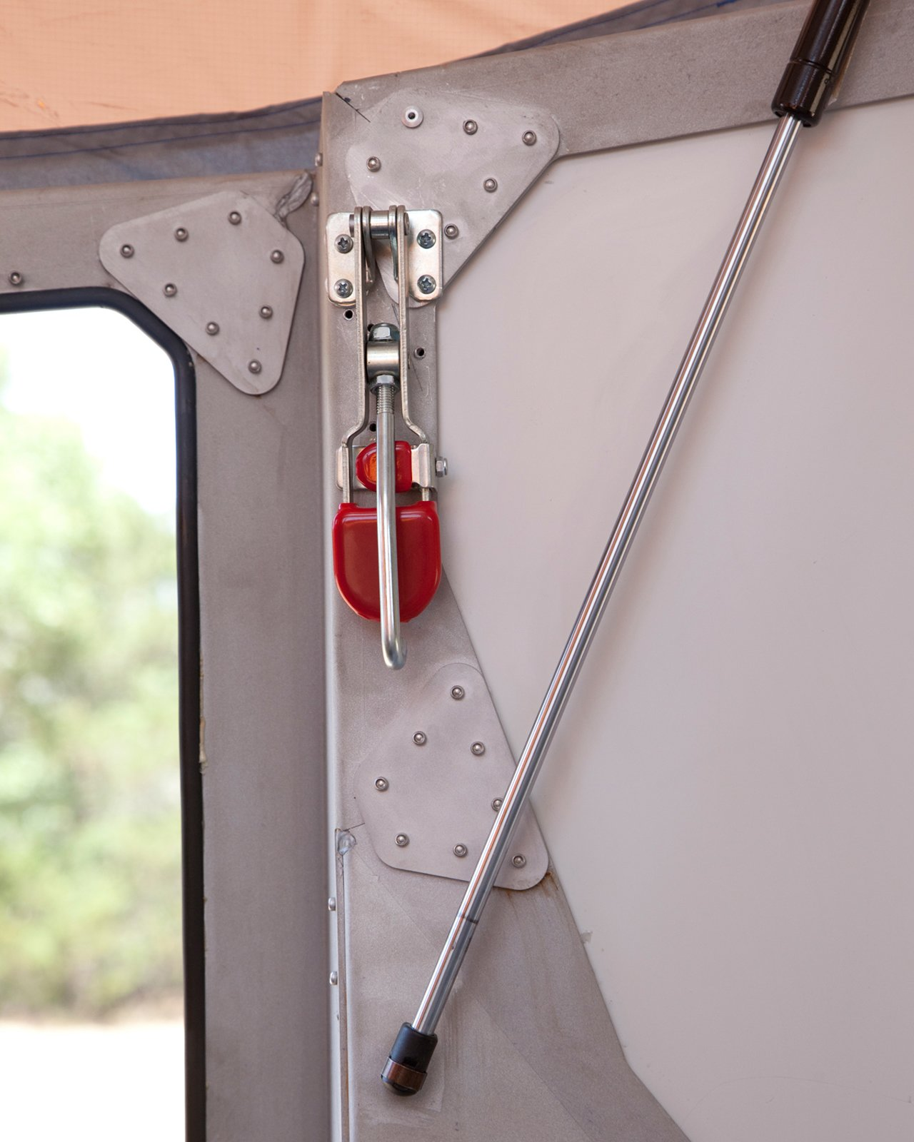 Hooks on the inside (like the mechanism with the red tab) latch into the camper's roof to help hold it down. Throughout the camper, small cricket images are laser-cut into the aluminum frame. The camper's name hints at its shape and is meant to conjure visions of sleeping under the stars with crickets chirping nearby.  Photo 13 of 15 in Modern NASA-Inspired Cricket Trailer