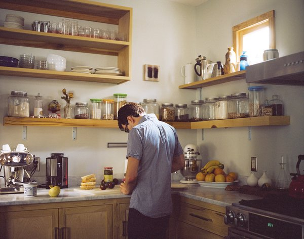 Josh Nissenboim prepares food in the kitchen. The countertop is Carrera marble, chosen because for its lightness and ability to wear in naturally.