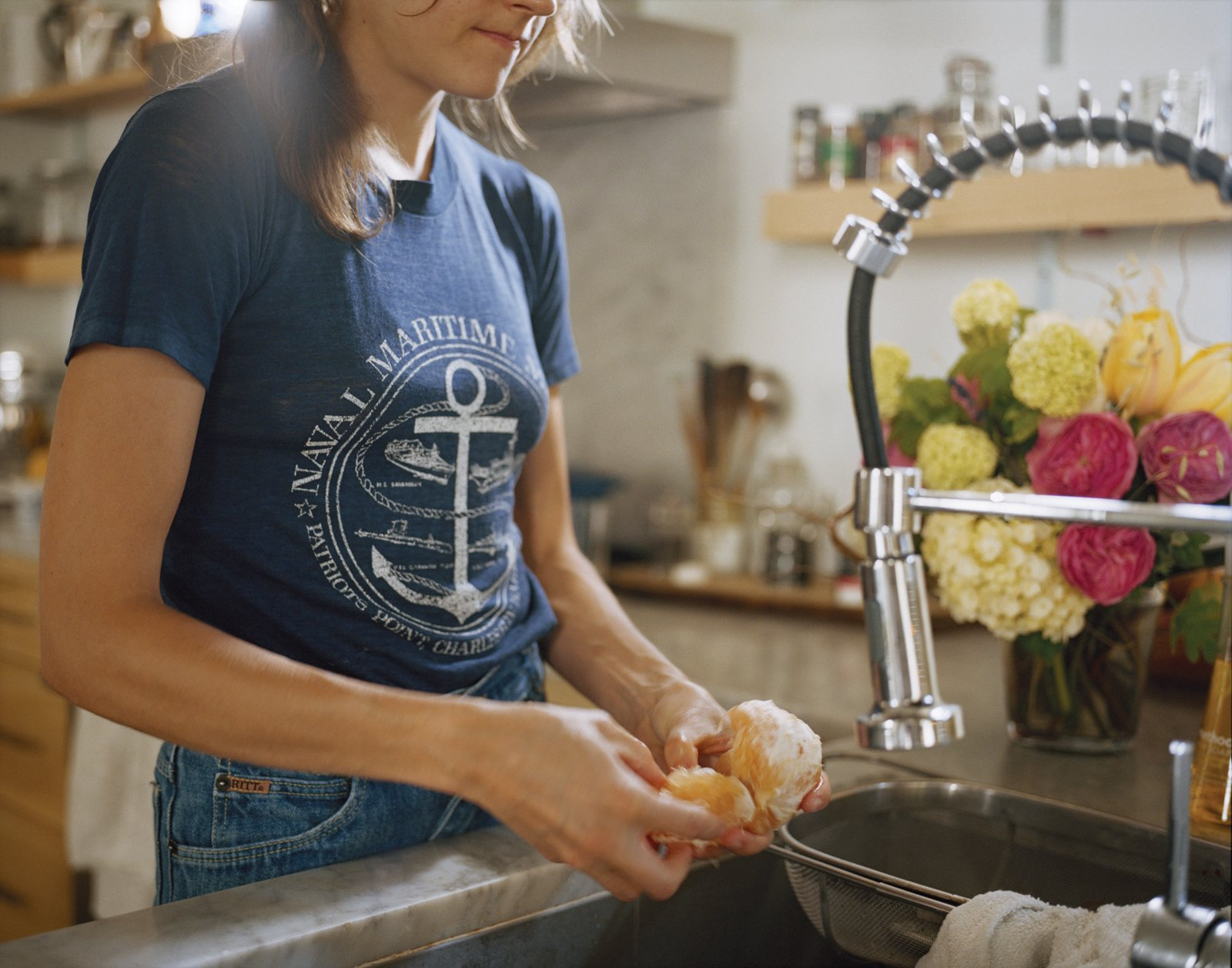Helen Nissenboim washes produce at the sink, which, along with the faucet, is made by Vigo and sourced from Overstock.com.  Photo 7 of 18 in Raise High the Roof Beams