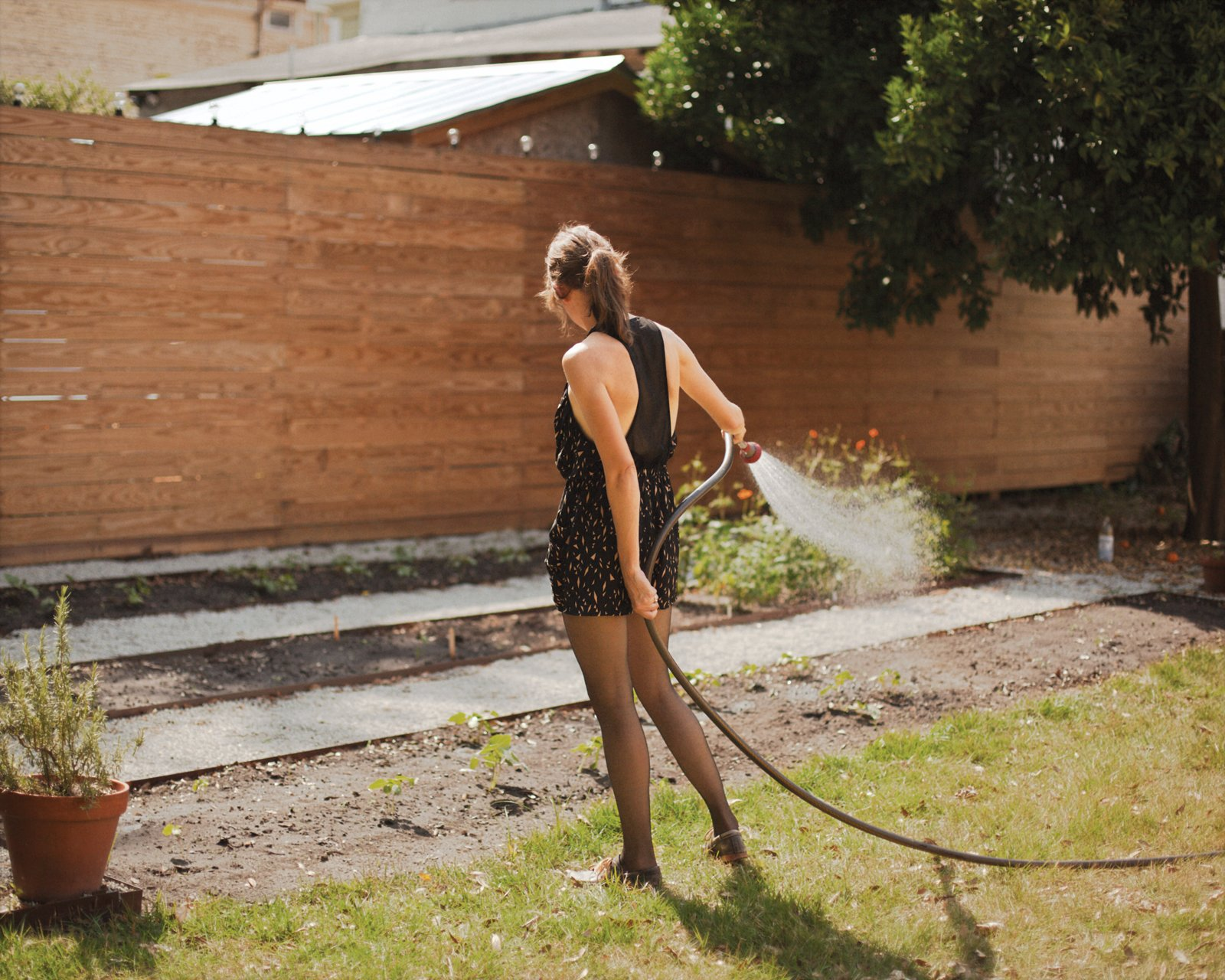 Helen Rice watering the garden outside of her Charleston residence.