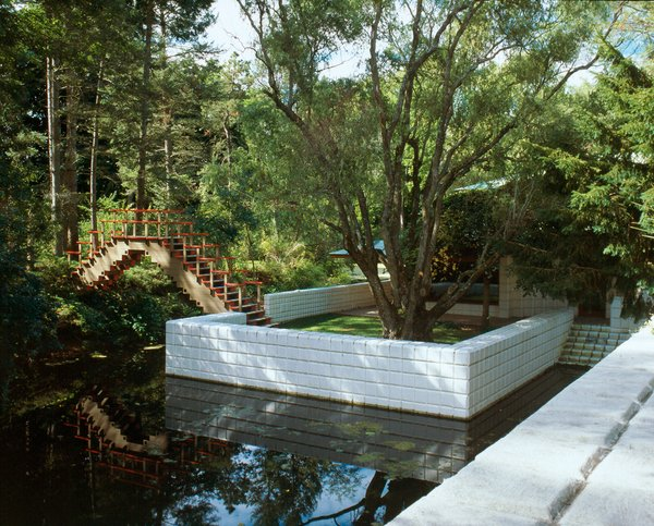 A geometric bridge connects one of the many outdoor terraces of the Dow Home to green space on the other side of the pond.