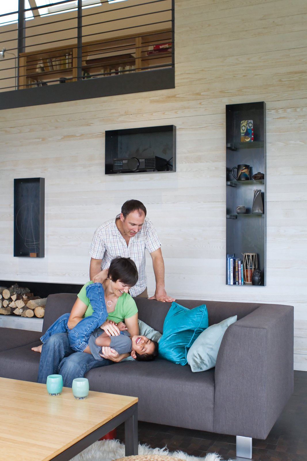 The open-plan living room and kitchen are a giant playground for five-year-old Suresh and his parents, as is the durable sofa and table base from Room & Board. Steel alcoves inset into the white-stained cedar wall shelter firewood, books, and treasured objects.  Photo 6 of 10 in An Epic Plot