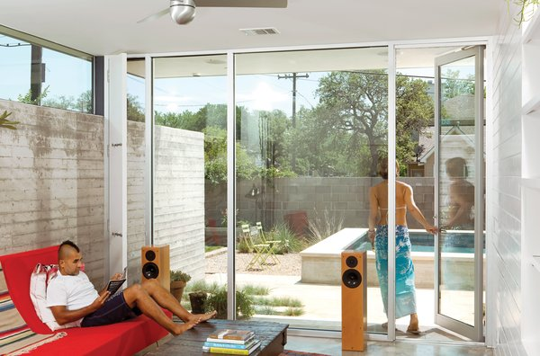 In the corners of the kitchen and living room, narrow screened doors let the southeast breezes flow through the home and allow the remaining glass windows to stay fixed and clear.