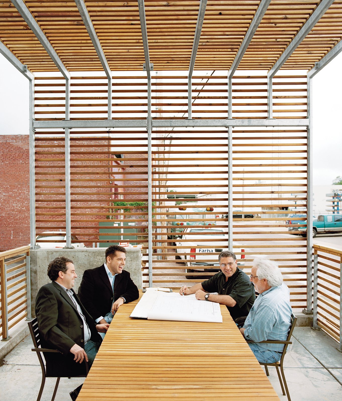 A patio protected by a steel-and-cedar-slat trellis accommodates a meeting between (left to right) contractor Mark Farha, building owners and developers Brock Oaks and David Farha, and owner and contractor Ted Farha.  Photo 6 of 13 in Building Community
