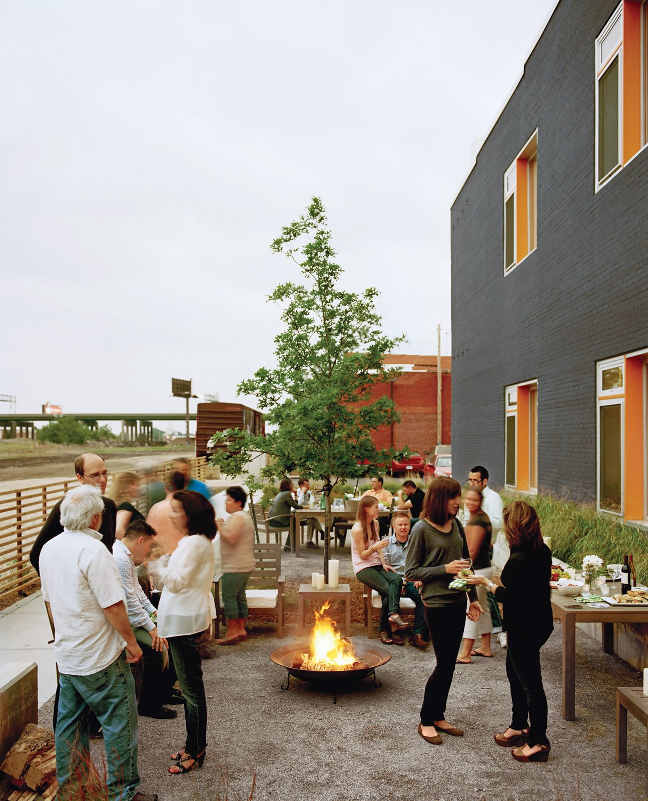 """Architect Douglas Stockman says the building's charcoal-and-orange exterior coloring was """"intended to reflect the dynamic character of the neighborhood."""" Here, it provides a festive backdrop to the residents' semi-annual Finn Lofts community party. Building Community - Photo 4 of 13"""