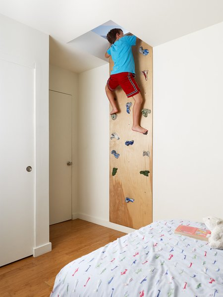 "Feldman designed to roof to have a slope optimal for solar panels. An added benefit is the ""secret"" playspace above the kids's rooms. To access the space, Feldman created this cork wall with climbing pulls purchased from a local sporting goods store."