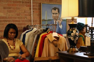 TVB is a-ok! A goofy portrait of President Nixon from Manly Vintage's booth keeps an eye on Jillian Knox of JJoules Vintage as she stocks a rack with fab vintage coats. <br><br>Photo by <br><br>Steven Pate